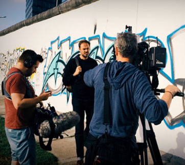 Local Producer on loacation at the remains of the Berlin Wall. When producing documentary, time is money and time is story telling time